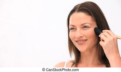 Woman applying makeup against a white background
