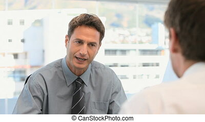 Businessman talking with a customer in his office