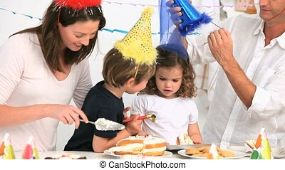 Mother giving cake to her children during a birthday party
