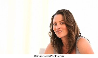 Beautiful woman smiling at the camera in the livingroom