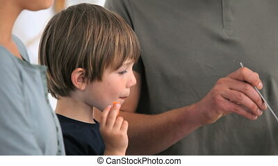Boy eating vegetables while his father is serving the plates