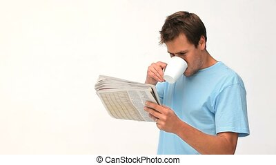 Man drinking a coffee while he is reading a newspaper