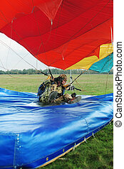 The landing moment of the parachutist in camouflage overalls...