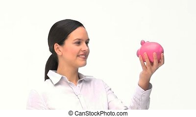 Woman putting dollars in a piggy bank against a white...