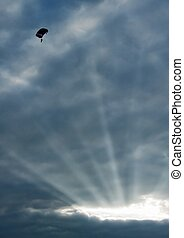 The parachutist under clouds of the evening sky is shined...