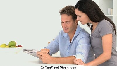 Man doing crosswords with his wife in the kitchen