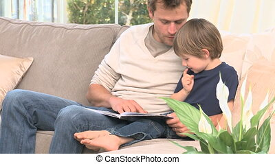 Man reading a book with his son in the livingroom
