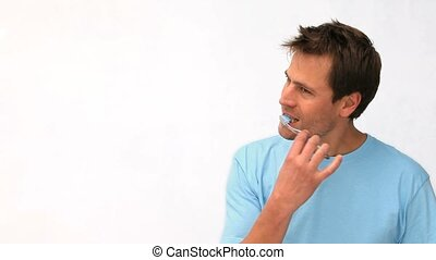 Man brushing his teeth against a white background