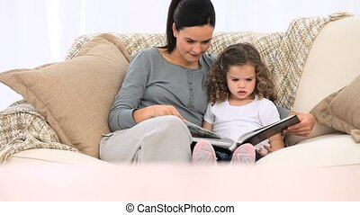 Mother looking at an album with her daughter sitting on the...