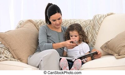 Mother and daughter looking at an album sitting on the sofa