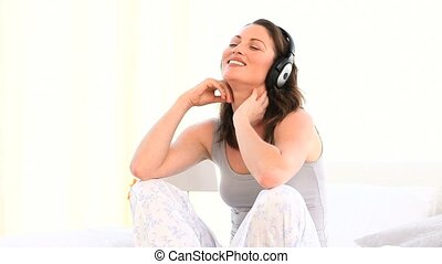 Superb woman listening music against a white background