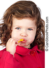 Adorable baby girl eating sweets isolated over white...