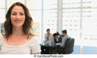 Businesswoman smiling to the camera while her team is...