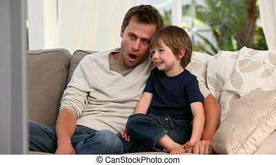 Attentive father watching tv with his son on their sofa