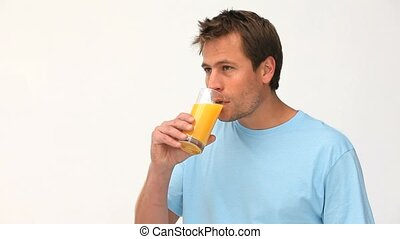 Cute man drinking a glass of orange juice
