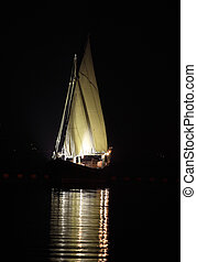 Arab dhow at night - An Arab dhow with its lateen sail lit...