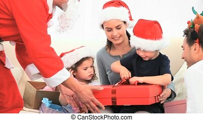 Santa Claus offering a gift to a little boy against a white...