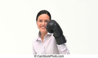 Smiling businesswoman boxing towards the camera against a...
