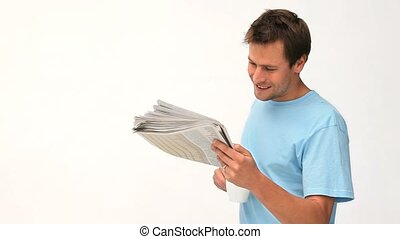Smiling man reading a newspaper against a white background
