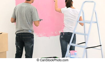 Nice couple painting the wall together at home
