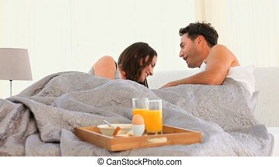 Joyful Couple having Breakfast in bed