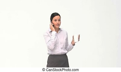 Businesswoman drinking while she is phoning against a white...