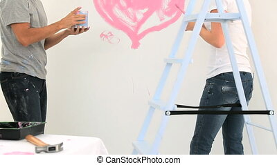 Beautiful couple painting together at home