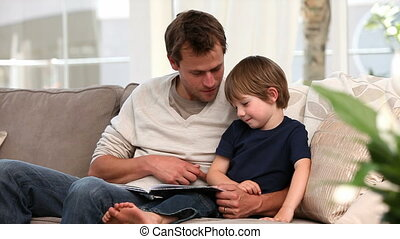 Nice father reading a story to his young son at home
