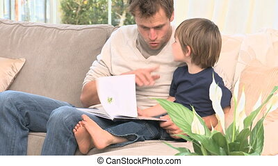 A dad reading a story to his son - A dad relading a story to...