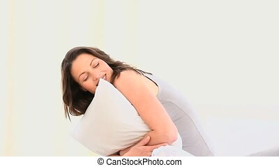 Beautiful women hugging her pillow against a white...
