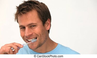 A man brushing his teeth against a white background
