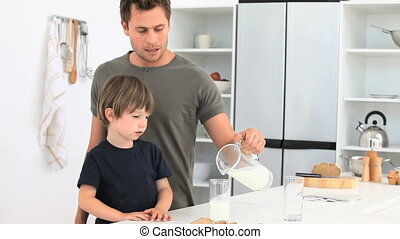 A dad serving a glass of milk to his son in the kitchen