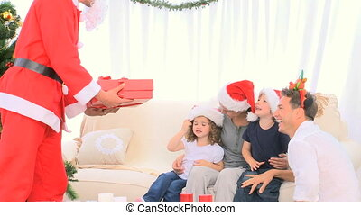 Santa Claus offering a gift to a little boy in the living...