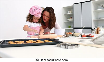 Adorable girl baking with her mother in the kitchen