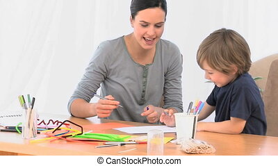 A mother drawing with her young son at home