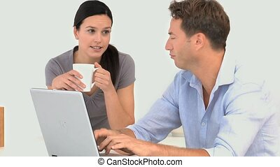 A couple talking around their laptop against a white...