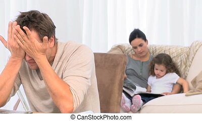 A desperate man on his laptop while his family is on the sofa