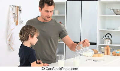 Attentive man serving a glass of milkto his son
