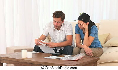 Couple calculating their domestic bills - Couple calculating...