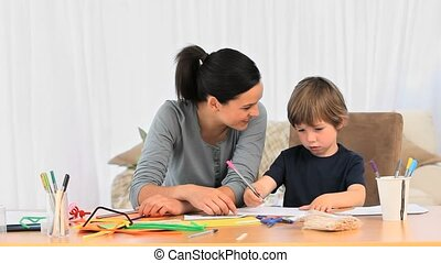 A mother talking with her son while he is drawing at home