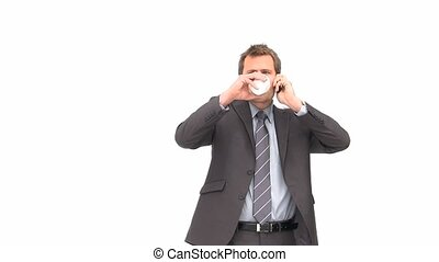 Businessman drinking while phoning against a white...