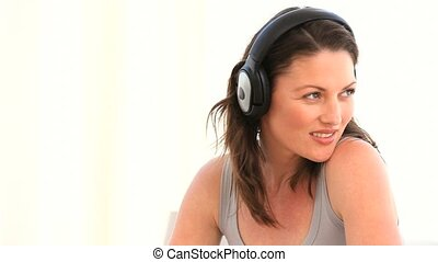 Lovely woman listening to music against a white background