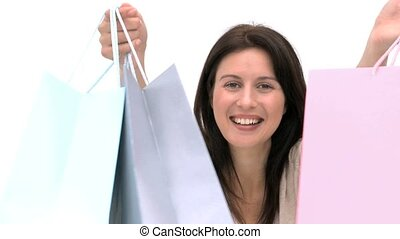Smiling woman with shopping bags against a whit background