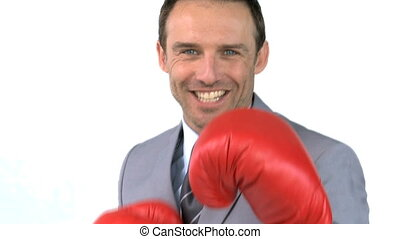 Smiling businessman with boxing gloves against a white...