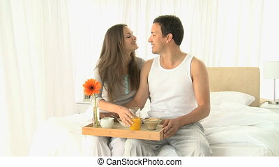 Lovely couple kissing each other while they having breakfast