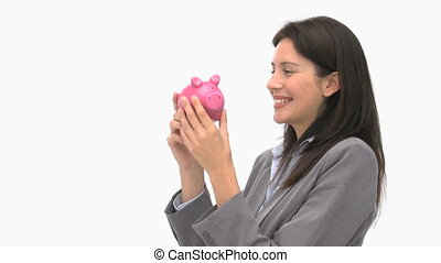 Smiling businesswoman holding a piggy bank against a white...