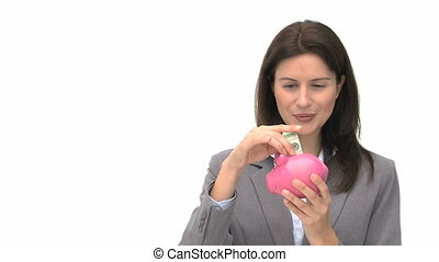 Smiling businesswoman saving money in a piggy bank against a...