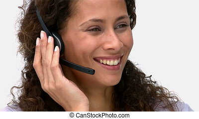 Closeup of a smiling businesswoman talking with headphones...