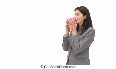 Businesswoman holding a piggy bank against a white...