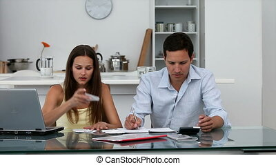 Serious couple calculating their bills while sitting at a...